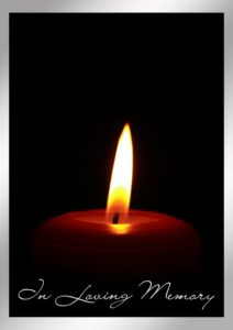 "Flame of a candle in a dimly lit room with ""In Loving Memory"" in script"