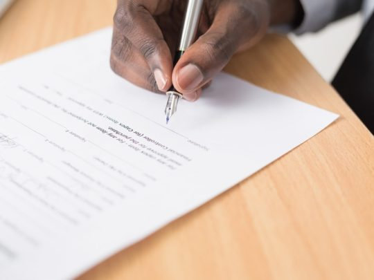A close-up of a man signing a power of attorney agreement after receiving advice from Funeralocity in New Orleans, LA