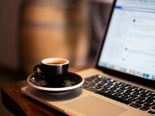 A small cup of coffee sitting on the edge of laptop
