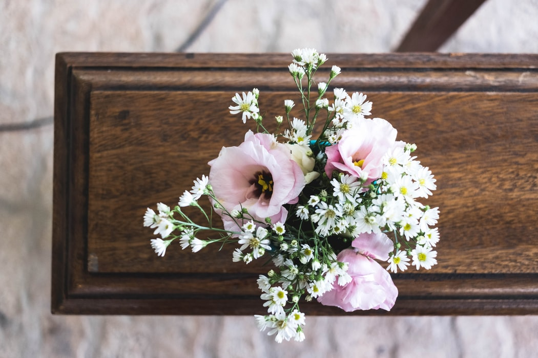 Pink and white flowers on top of a casket for a direct burial at a funeral home found on Funeralocity in New York, NY